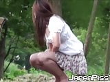 Tantalizing Japanese in skirt peeing behind bench in park